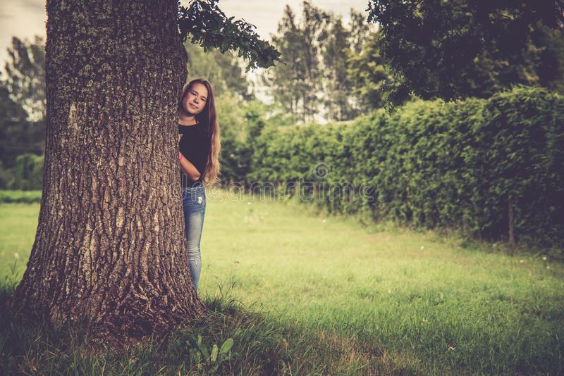 Teen girl in nature near tree royalty free stock photography
