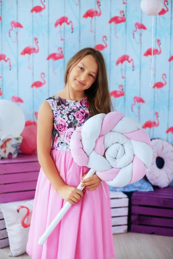Teen girl in a pink dress in the room. The concept of childhood stock photography
