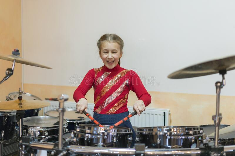 Teen girl playing the drums. Teen girls are having fun playing drum sets in music class.  stock image