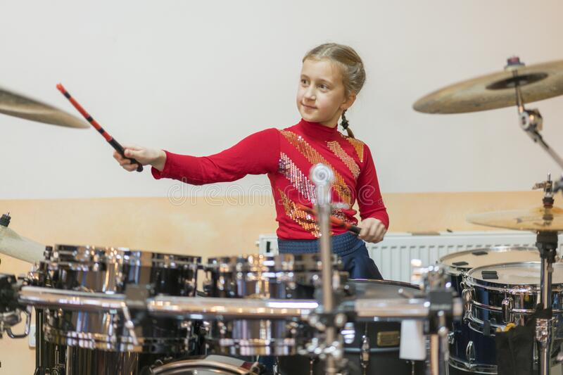 Teen girl playing the drums. Teen girls are having fun playing drum sets in music class. Girl in red drumming stock images