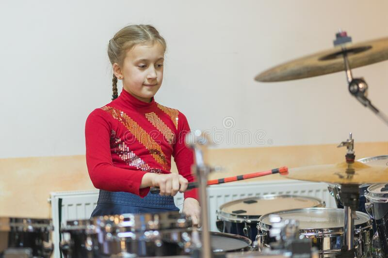 Teen girl playing the drums. Teen girls are having fun playing drum sets in music class. Girl in red drumming stock image