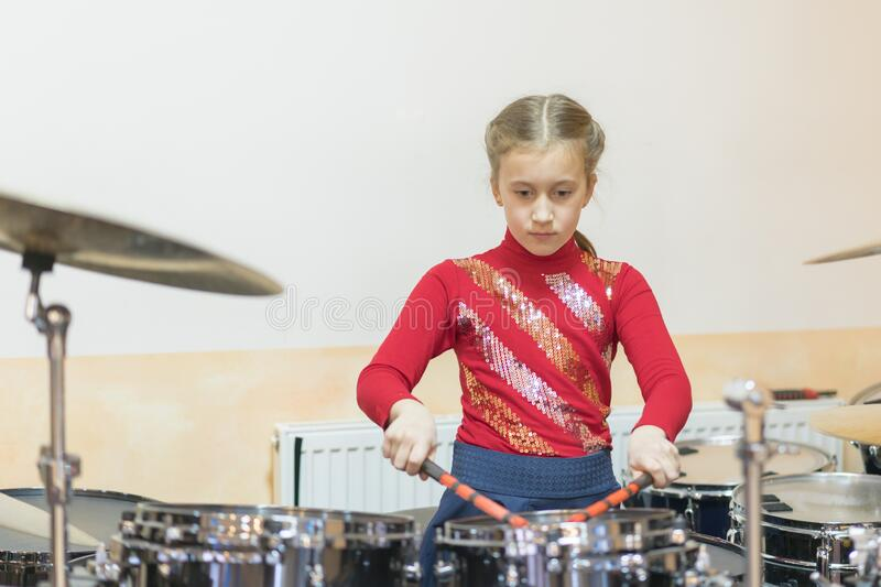 Teen girl playing the drums. Teen girls are having fun playing drum sets in music class royalty free stock photos