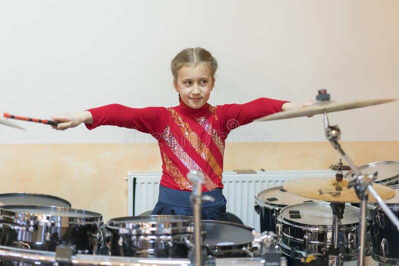 Teen girl playing the drums. Teen girls are having fun playing drum sets in music class royalty free stock image