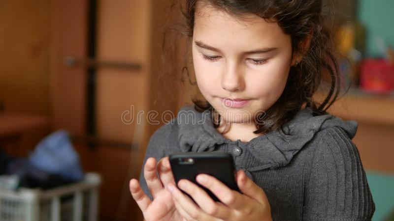 Teen girl playing online games on your smartphone school. Teen girl playing online games on your smartphone online stock photography