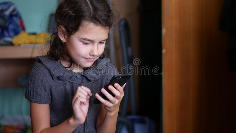 Teen girl playing online school games on your smartphone. Teen girl playing online school girl games on your smartphone stock image
