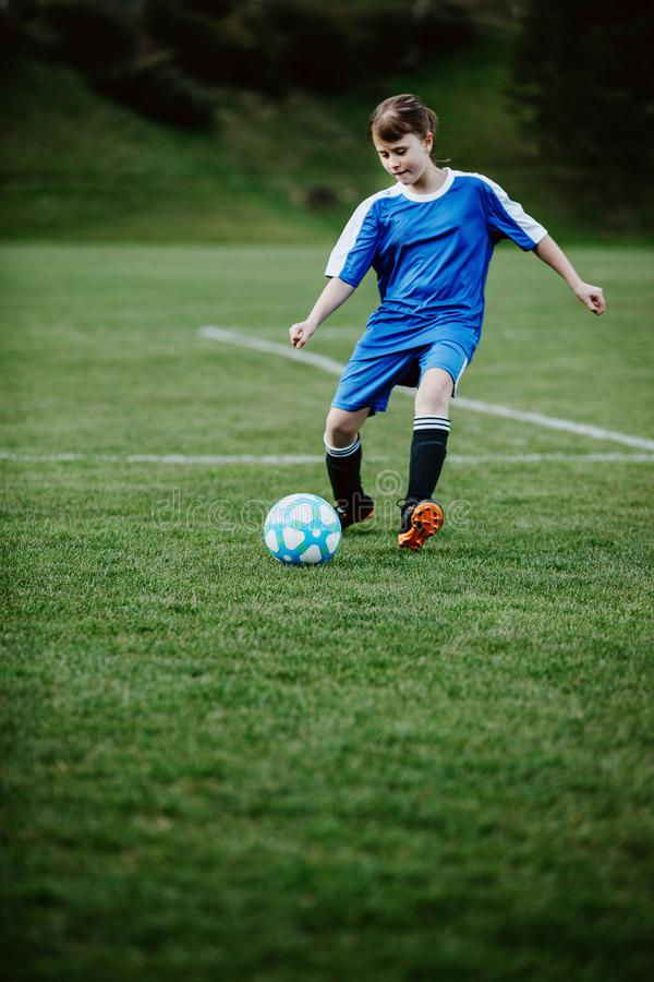 Teen girl playing soccer at local stadium outside on grass field. Kicking the ball. Children playing football, favourite sport, football fever worldwide stock photo