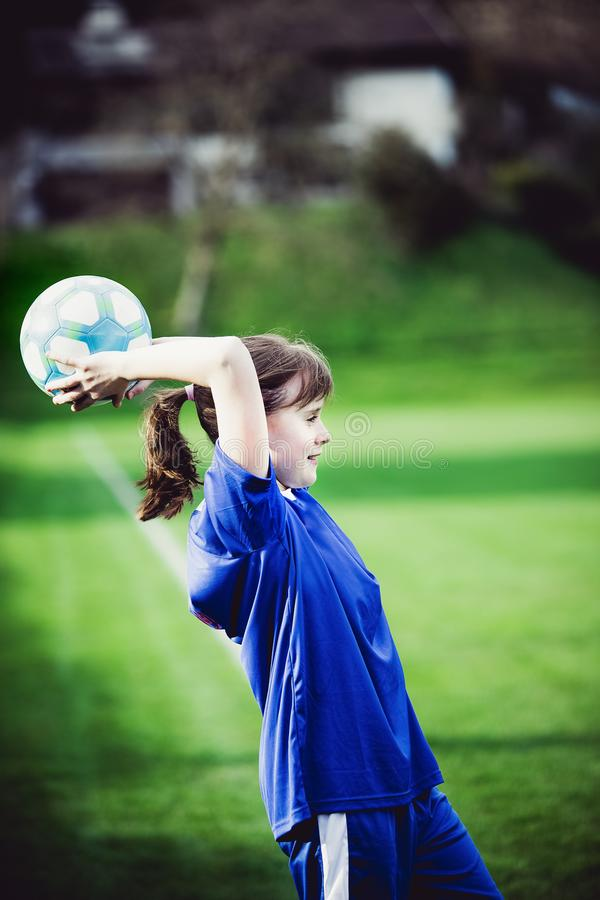 Teen girl playing soccer at local stadium outside on grass field. Making throw-in with the ball. Children playing football. Favourite sport, football fever royalty free stock photography