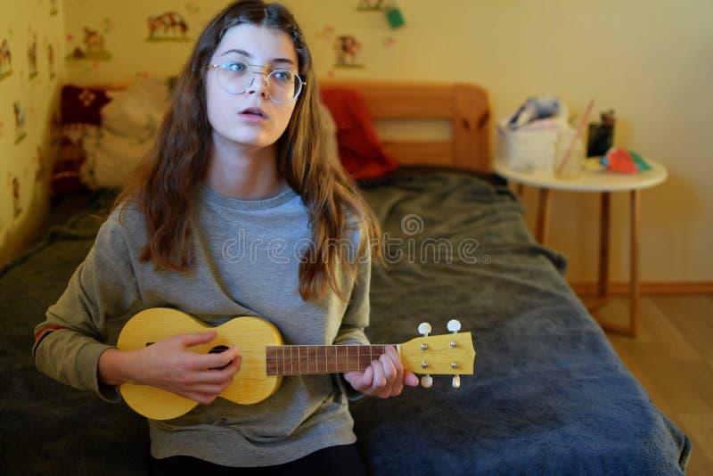 Teen girl playing ukulele guitar royalty free stock images