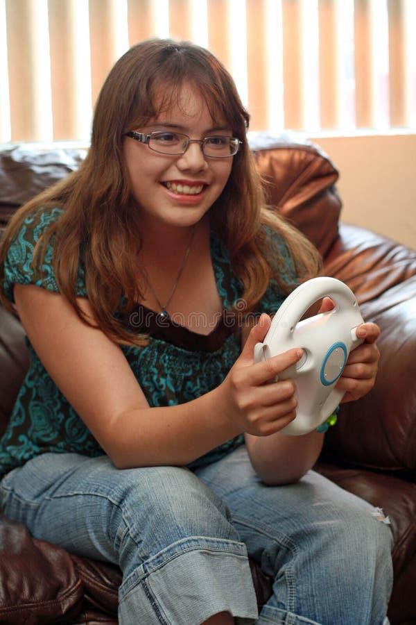 Teen girl plays video race game stock photos