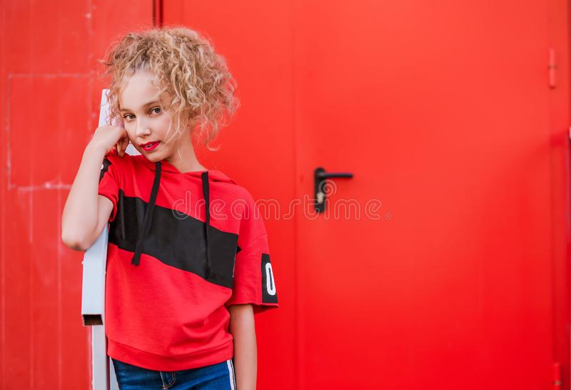 Teen girl posing on red wall background stock images