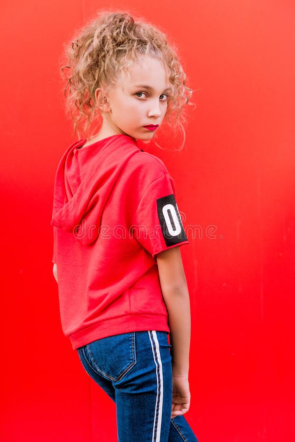 Teen girl posing on red wall background royalty free stock photos