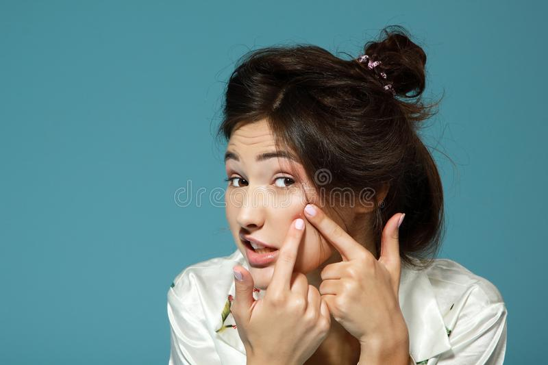 Teen girl with problem skin look at pimple. Morning theme. stock photography