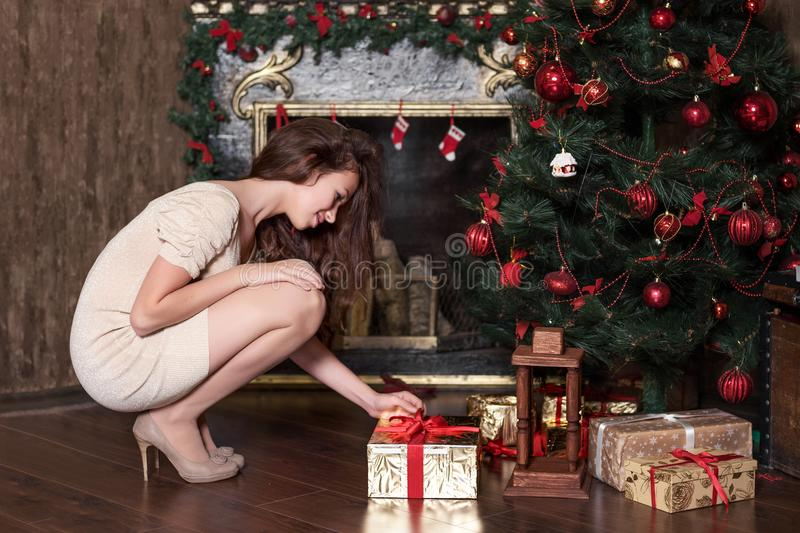 Young girl teenager puts under the Christmas tree gift squatting near the new year decorated fireplace royalty free stock photos
