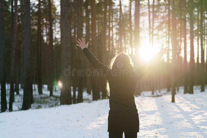 Teen girl raised hands from behind in winter pine forest in sunset stock photos