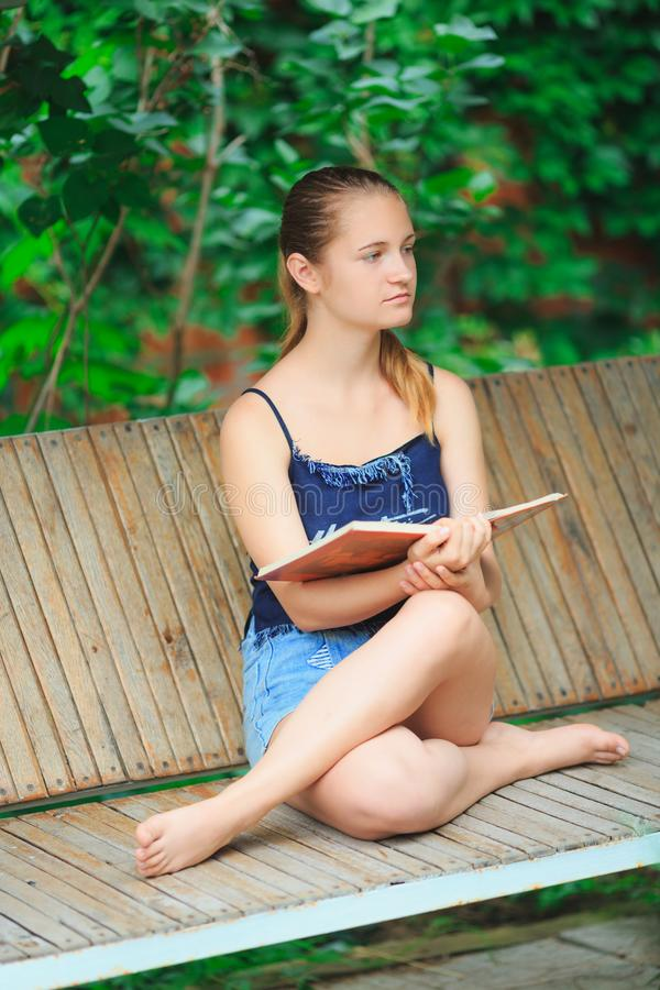 Teen girl reading a book and dreaming royalty free stock images