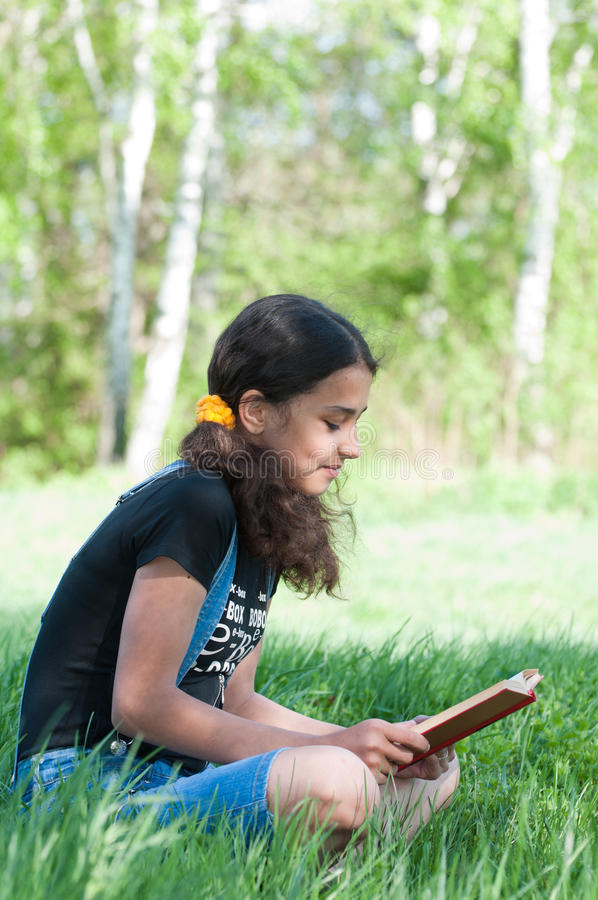 Teen girl reading book on nature stock image