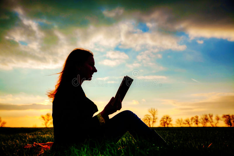 Teen girl reading book outdoors royalty free stock photos