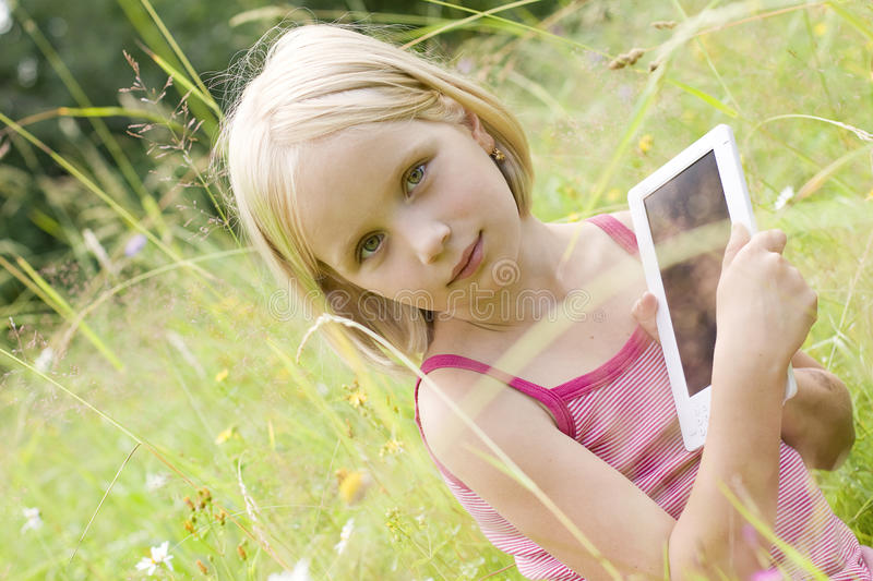 Download Teen girl reading e-book stock image. Image of cute, grass - 23077903