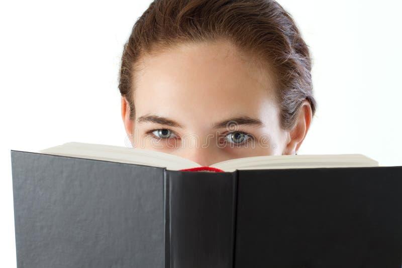 Teen girl reading, looking over the book stock photos