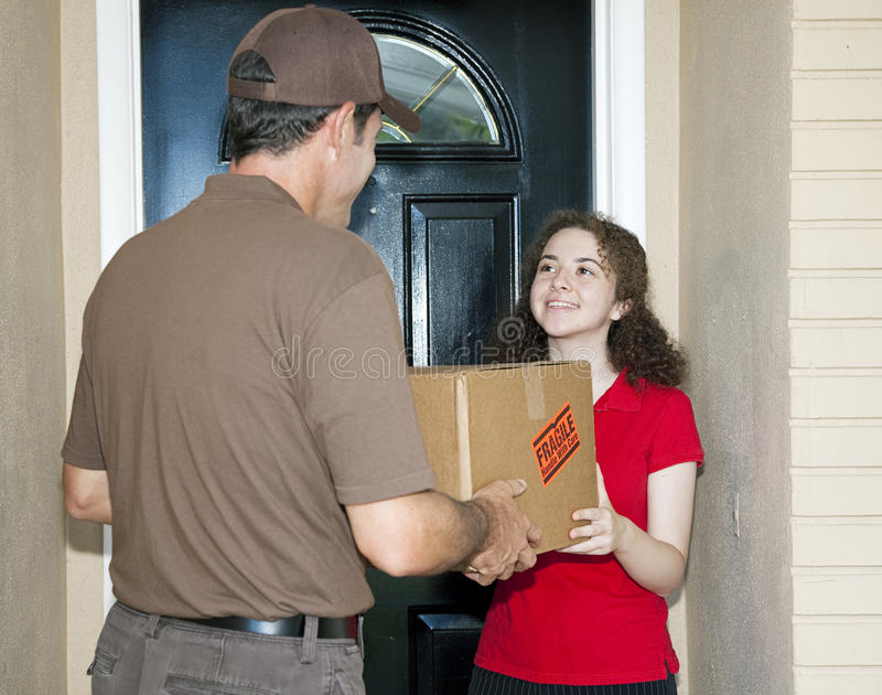 Teen Girl Receives Delivery. Teen girl receives package from friendly delivery man royalty free stock photography