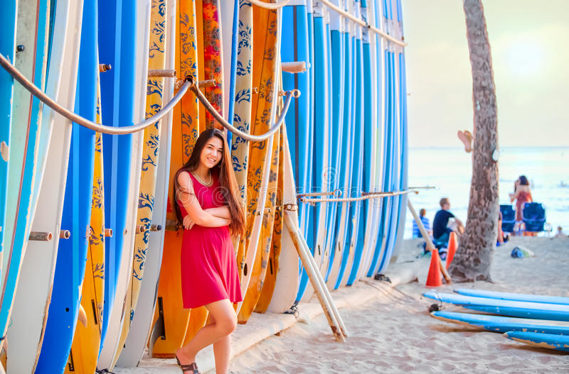 Teen girl in red dress leaning by surfboards on beach. Beautiful biracial teen girl in red dress leaning against rack of surfboardson beach in Hawaii stock images