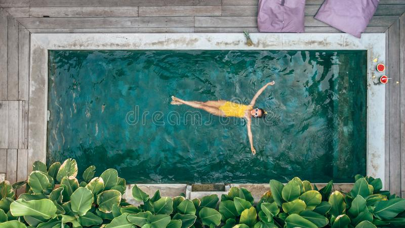 Girl relaxing in pool on Bali villa. Teen girl relaxing at pool on Bali private villa, top view from above royalty free stock photography