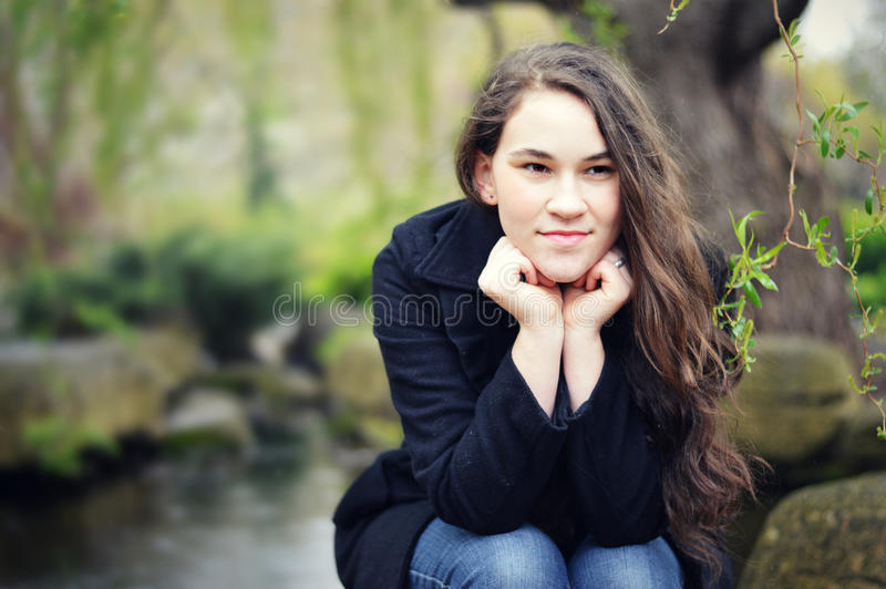 Teen Girl Resting Head on Hands by Pond. A teen girl with long brown hair, wearing a black dress coat and blue jeans resting her head on her hands as she gazes royalty free stock photo