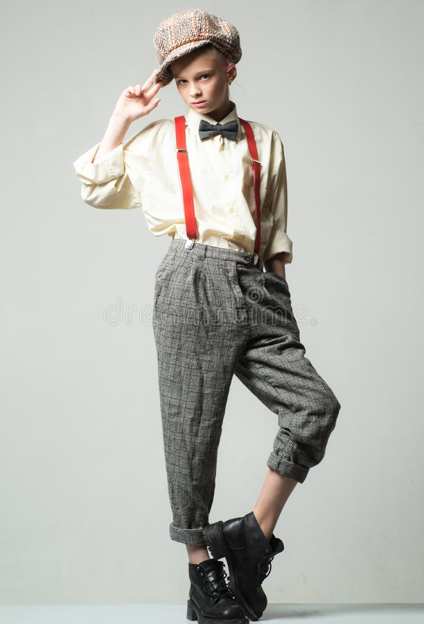 Teen girl in retro male suit. retro fashion model. vintage charleston party. suspender and bow tie. old fashioned child. In checkered beret. vintage english royalty free stock image
