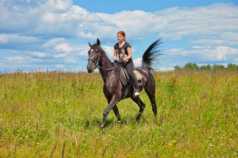 Teen girl rides on the field with grass on a Sunny summer day. royalty free stock image
