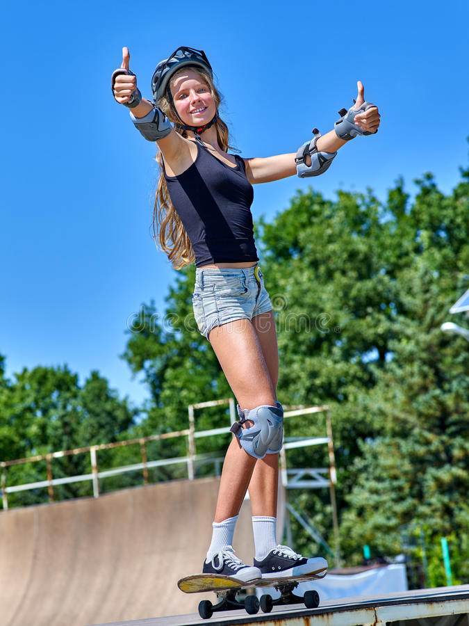 Teen girl rides his skateboard. Outdoor. Girl thumb up aganist blue sky royalty free stock images