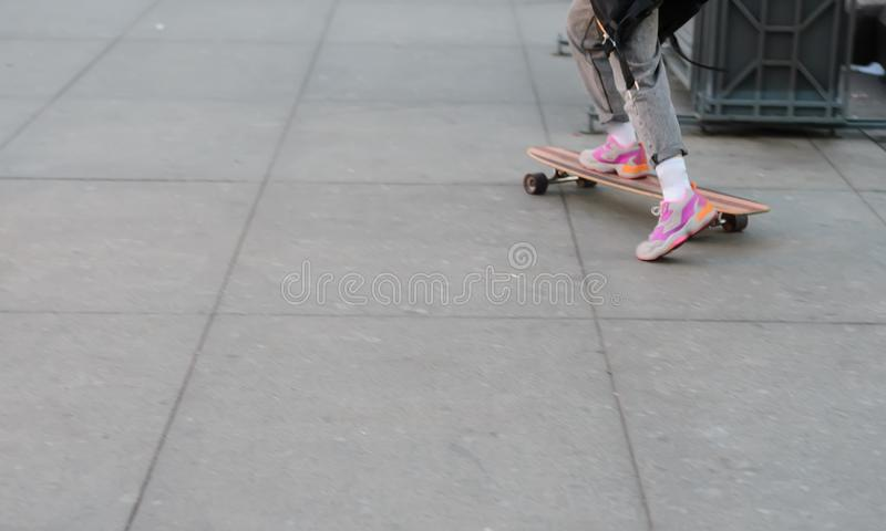 Teen girl rides a skateboard in the town square. stock image