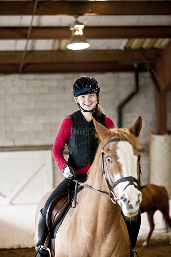 Teen girl riding horse royalty free stock image