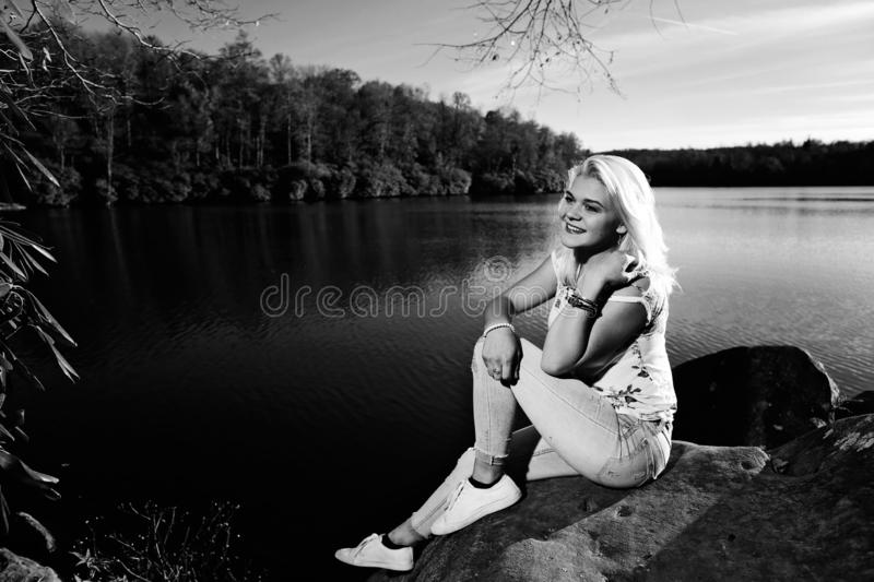 Teen girl on a rock by the lake royalty free stock image