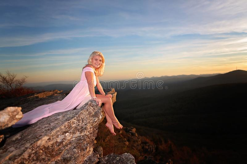 Teen girl on a rock overlook in the mountains royalty free stock images