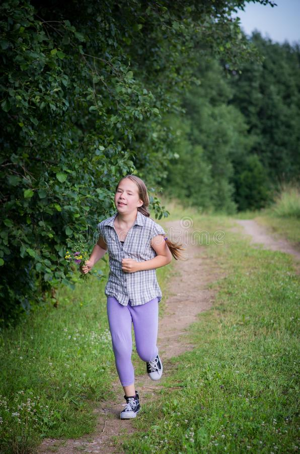 Teen girl running in forest. Summer time royalty free stock photos