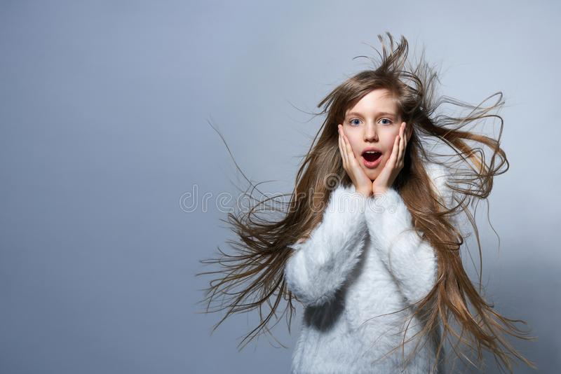 Teen girl screaming of surprise. Teen girl with long hair flying in air screaming of surprise, over studio grey background royalty free stock photos