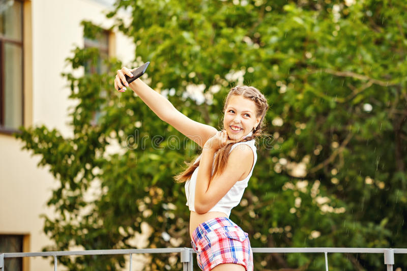 Teen Girl selfie. Teenage Girl photographing herself on a cell phone. Young fashion. Self-portrait. Selfie royalty free stock image