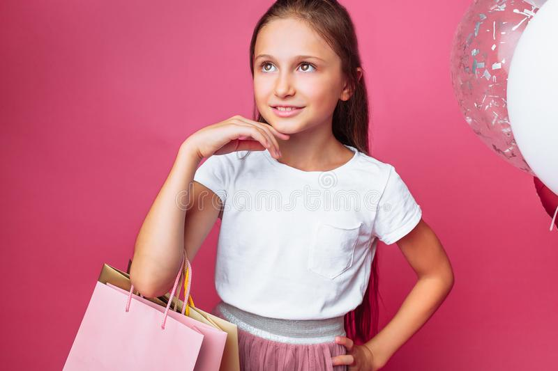 Teen girl with shopping bags in hand, on pink background, with balloons stock image