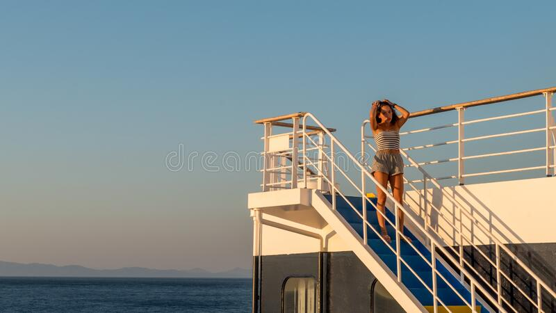 Teen girl in shorts standing on top of blue stairway on ferry boat royalty free stock photos