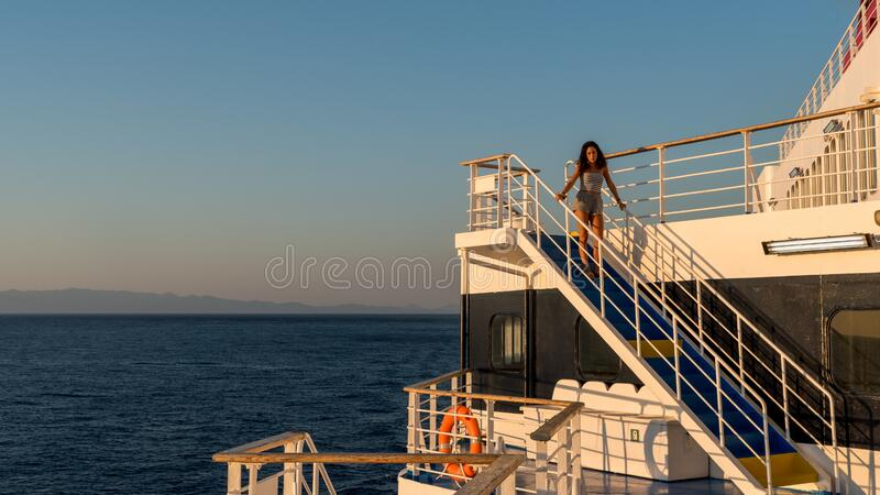 Teen girl in shorts standing on top of blue stairway on ferry boat royalty free stock photo