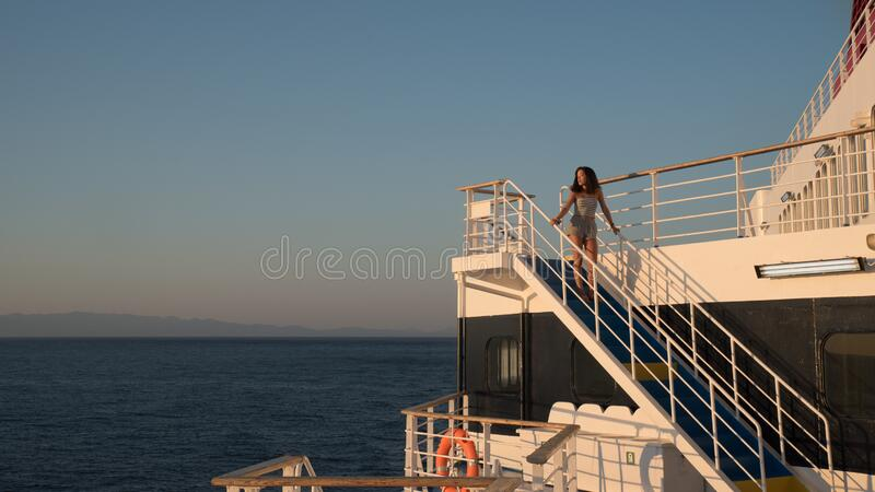 Teen girl in shorts standing on top of blue stairway on ferry boat royalty free stock photography