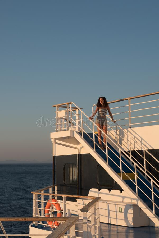 Teen girl in shorts standing on top of blue stairway on ferry boat royalty free stock images