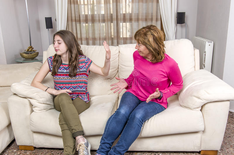 Teen girl is showing stop gesture to angry mother while sitting. On sofa at home royalty free stock photo