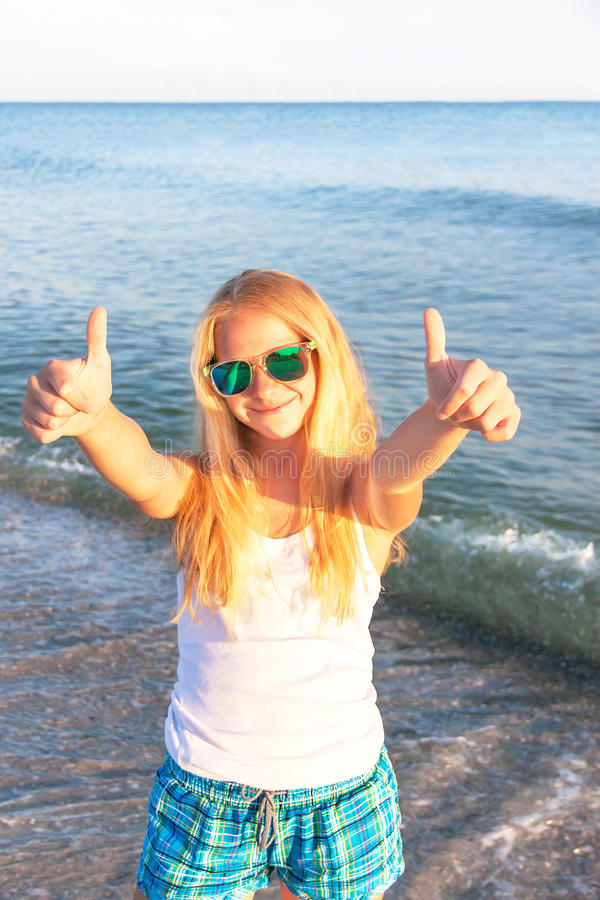 Teen girl showing thumbs up on the sea background. stock image