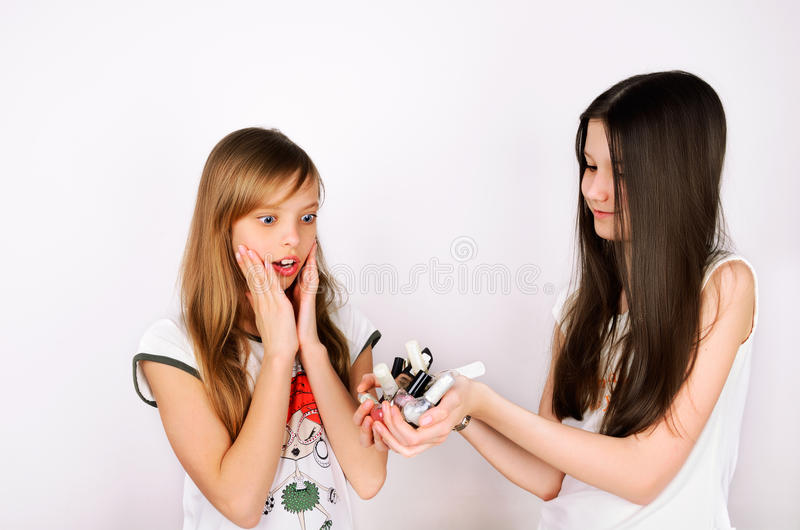 Teen girl shows her friend a lot of bottles of nail polish royalty free stock image