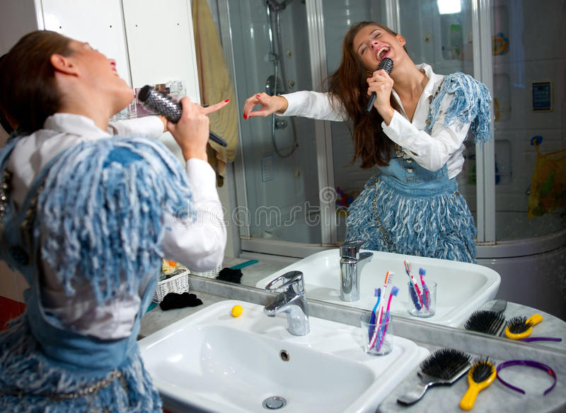 Teen girl singing. In the bathroom in front of the mirror royalty free stock photos