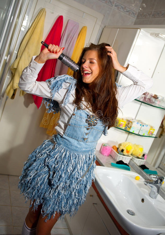 Teen girl singing. In the bathroom royalty free stock image