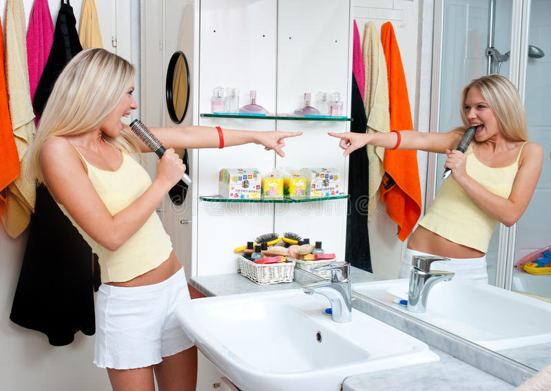 Teen girl singing in bathroom. Attractive teen girl singing in the bathroom royalty free stock photography