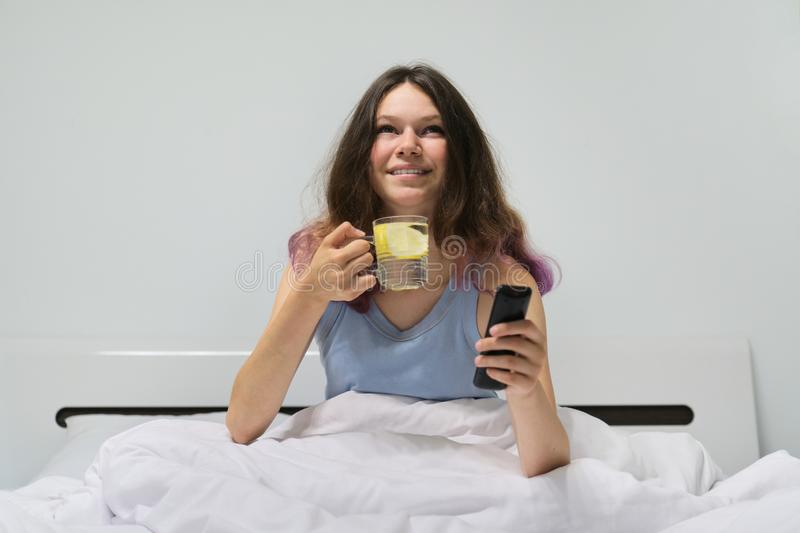 Teen girl sitting in bed with glass of water with lemon holding TV remote in hand stock photo