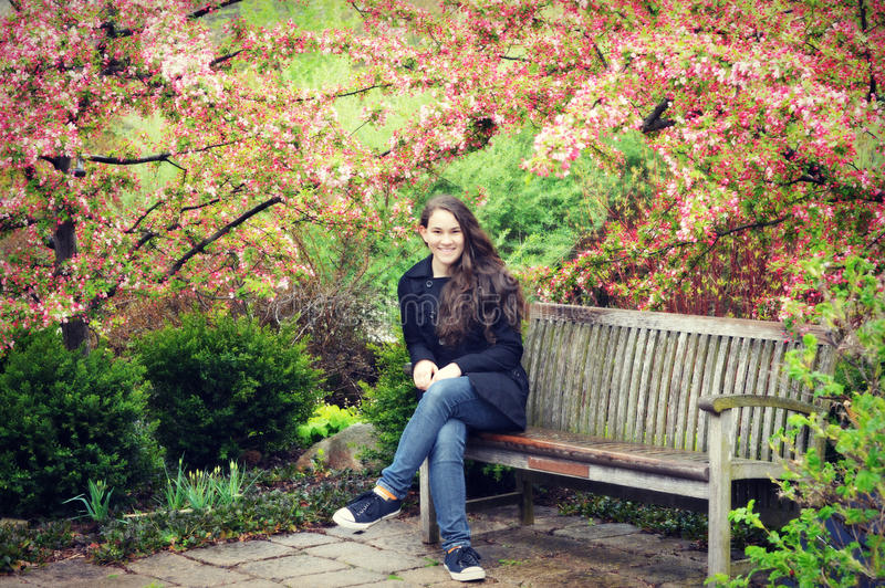 Teen Girl Sitting on Bench with Crab Apple Blossoms stock photography